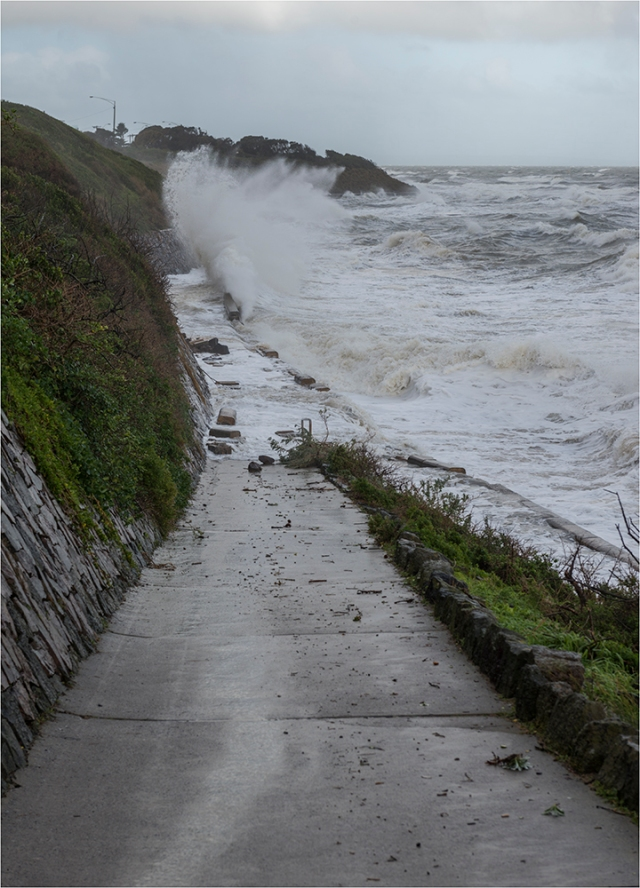 Huge waves break over the sea wall.